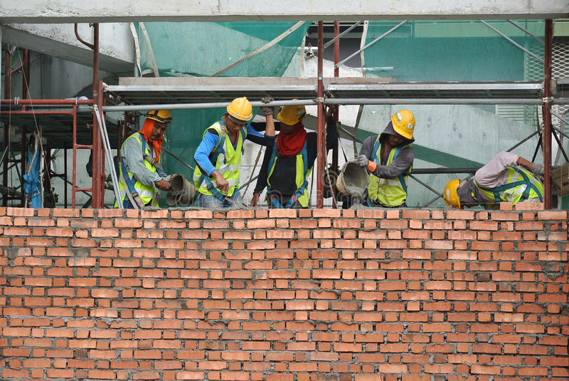 Trabalhadores da construção que colocam tijolos no canteiro de obras fotografia de stock