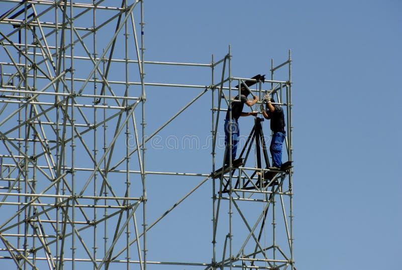 Trabalhadores da construção que constroem uma estrutura nova imagem de stock