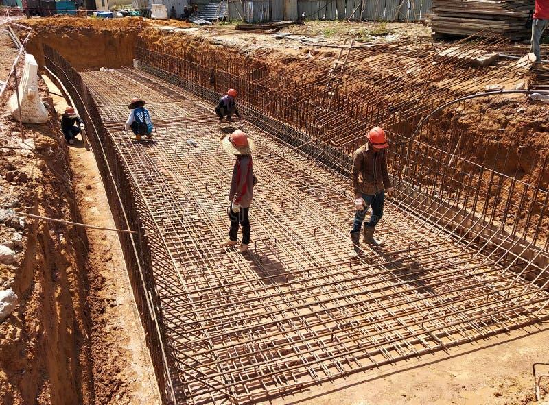 Trabalhadores da construção que fabricam a barra de aço do reforço para formar o concreto do reforço fotografia de stock