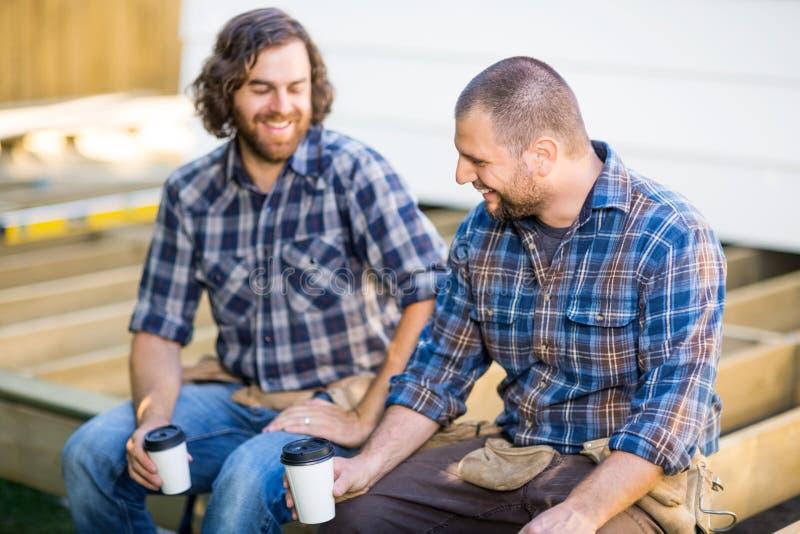 Trabalhadores da construção que guardam o café descartável imagem de stock royalty free