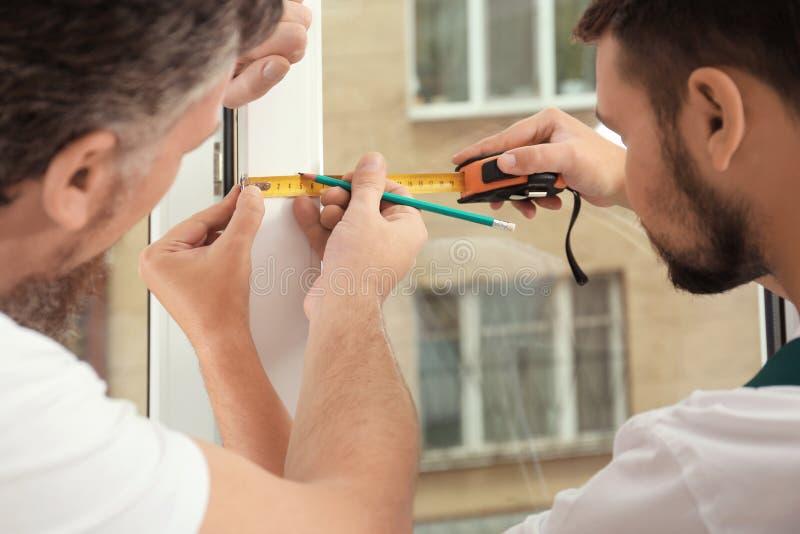 Trabalhadores da construção que instalam a nova janela imagens de stock royalty free