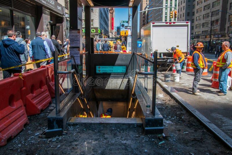 Trabalhadores da construção que substituem o passeio em torno da entrada ao metro do trem de F na rua do oeste 54th em Manhattan foto de stock