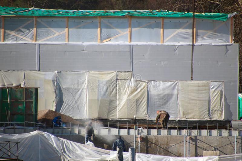 Trabalhadores da construção que trabalham em um canteiro de obras com paredes filme-cobertas foto de stock royalty free