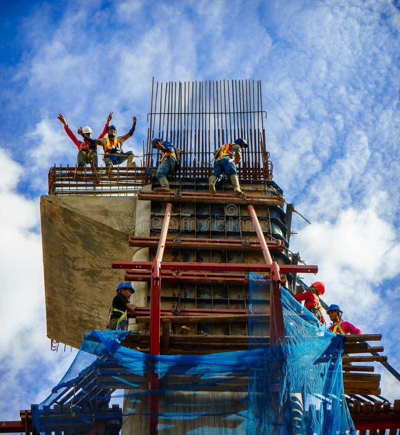 Trabalhadores da construção que trabalham no andaime imagens de stock