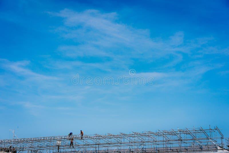 Trabalhadores da construção que trabalham no andaime Céu azul no fundo fotos de stock royalty free