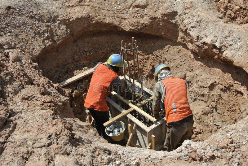 Trabalhadores da construção que usam o moedor para cortar o aço fotografia de stock