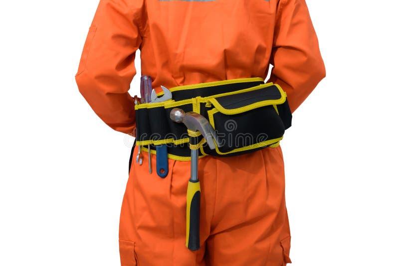 Trabalhadores da construção que vestem a roupa protetora alaranjada, capacete com a correia da ferramenta isolada no backround br fotos de stock royalty free
