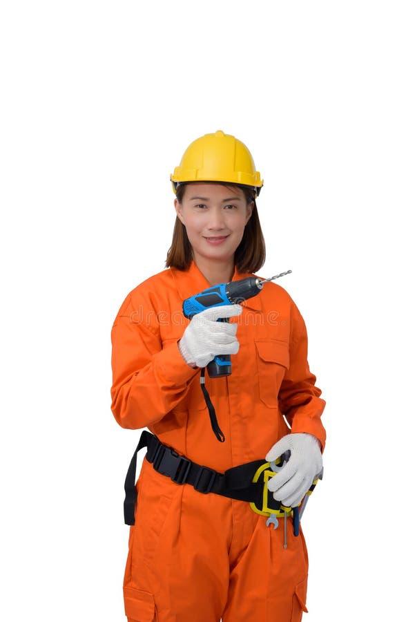 Trabalhadores da construção que vestem a roupa protetora alaranjada, mão do capacete que guarda a broca elétrica com a correia da fotos de stock