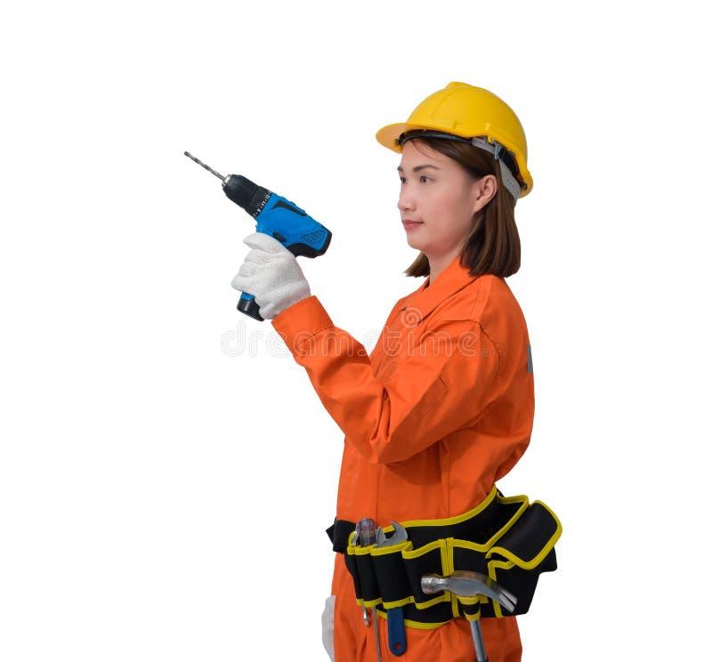 Trabalhadores da construção que vestem a roupa protetora alaranjada, mão do capacete que guarda a broca elétrica com a correia da imagens de stock royalty free