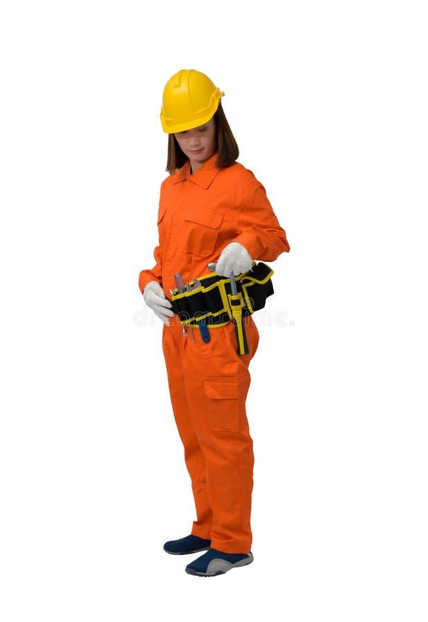 Trabalhadores da construção que vestem a roupa protetora alaranjada, martelo da terra arrendada da mão do capacete com a correia  fotografia de stock