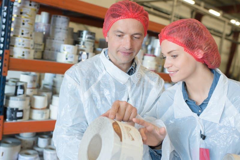 Trabalhadores da equipe na fábrica da fita adesiva foto de stock