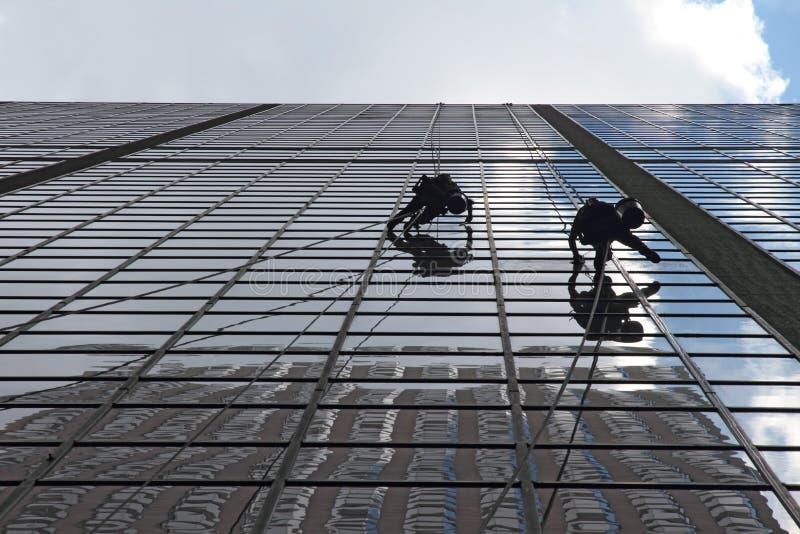 Trabalhadores da manutenção que escalam fora de um arranha-céus imagem de stock