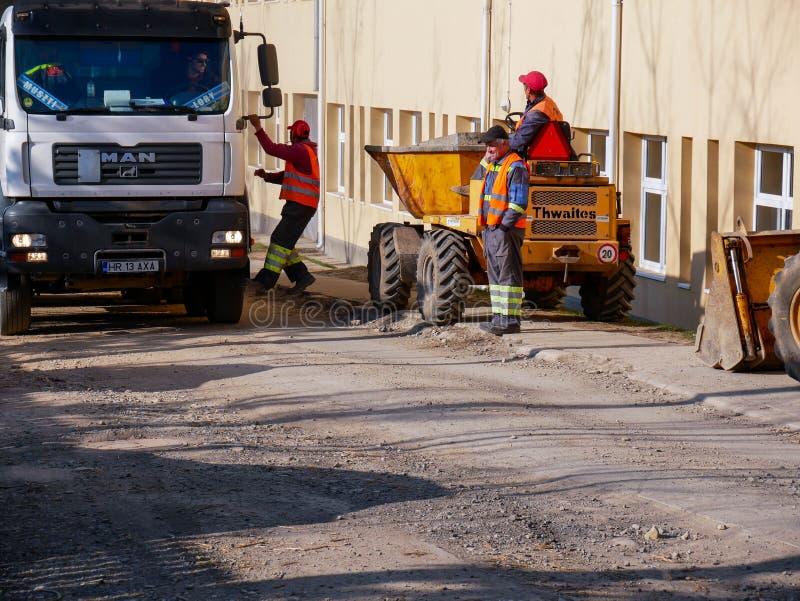 Trabalhadores de construção de estradas que sorriem, rindo do fim do dia útil imagem de stock