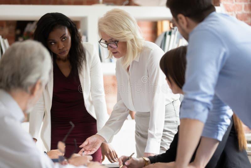 Trabalhadores de ensino do supervisor sério da mulher de negócio maduro na reunião de grupo foto de stock royalty free