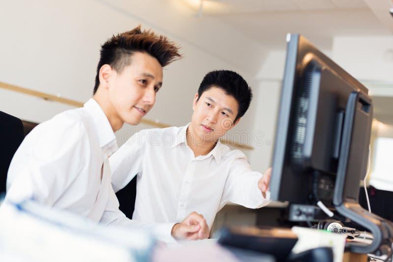 Trabalhadores de escritório asiáticos novos em sua mesa imagens de stock royalty free