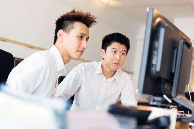 Trabalhadores de escritório asiáticos novos em sua mesa imagens de stock