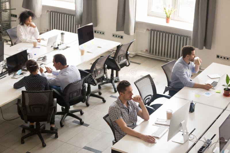 Trabalhadores de escritório diversos que usam computadores no espaço incorporado moderno foto de stock royalty free