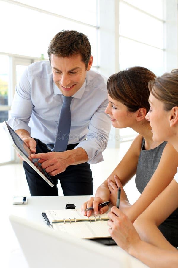 Trabalhadores de escritório em torno da tabela fotografia de stock royalty free