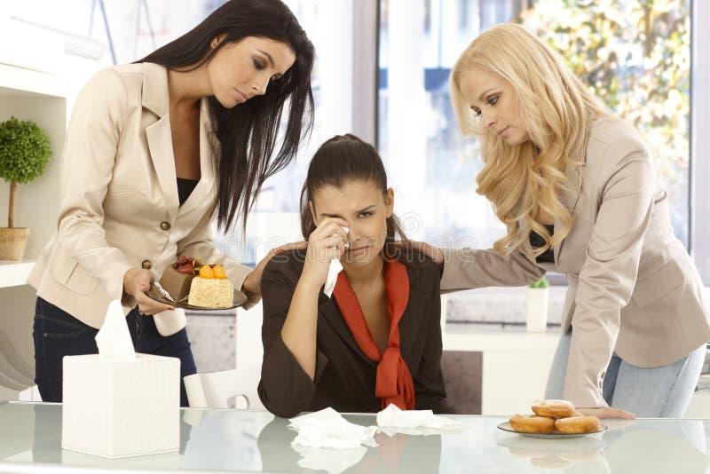 Trabalhadores de escritório novos que consolam o colega de grito fotografia de stock royalty free