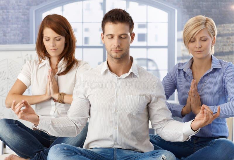 Trabalhadores de escritório que meditating no trabalho foto de stock royalty free