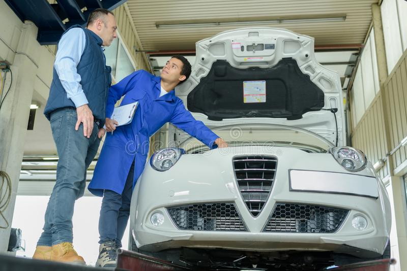 Trabalhadores de sorriso que fixam o motor de automóveis na garagem imagens de stock royalty free
