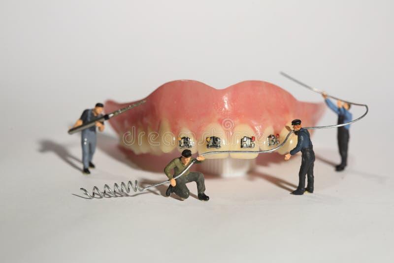 Trabalhadores diminutos que executam procedimentos dentais Escritório dental AR imagem de stock royalty free