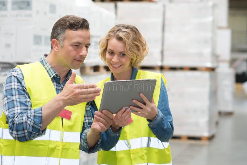 Trabalhadores do armazém na oficina usando a tabuleta digital fotos de stock