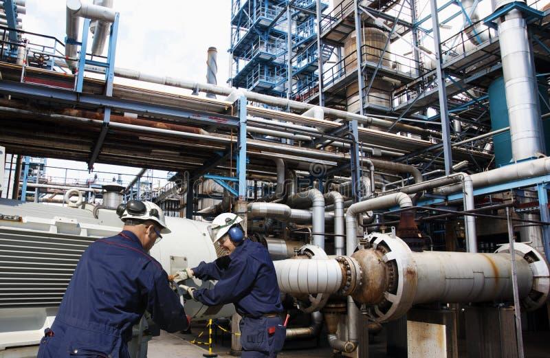 Trabalhadores do petróleo e gás dentro da grande indústria da refinaria fotografia de stock royalty free