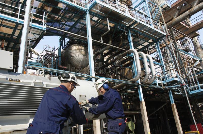 Trabalhadores do petróleo e gás dentro da refinaria imagem de stock