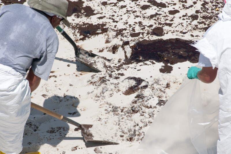 Trabalhadores do petróleo na praia imagem de stock