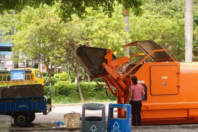 Trabalhadores do saneamento que carregam e que descarregam o lixo imagens de stock royalty free