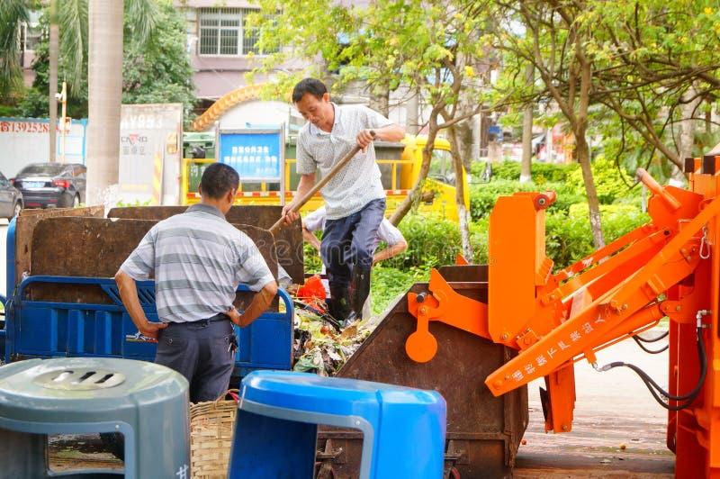 Trabalhadores do saneamento que carregam e que descarregam o lixo fotos de stock