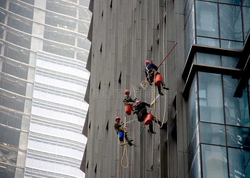 Trabalhadores do saneamento que limpam o arranha-céus foto de stock