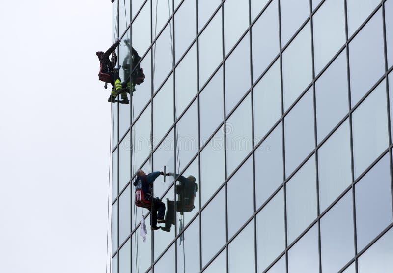 Trabalhadores do saneamento que limpam o hotel de vidro da fachada imagens de stock