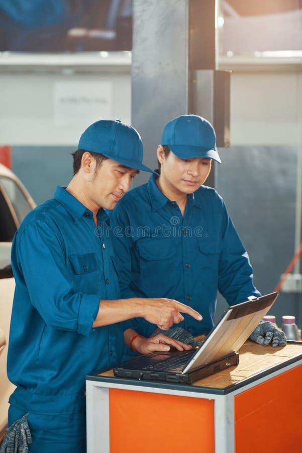 Trabalhadores do serviço de carros lendo e-mails foto de stock