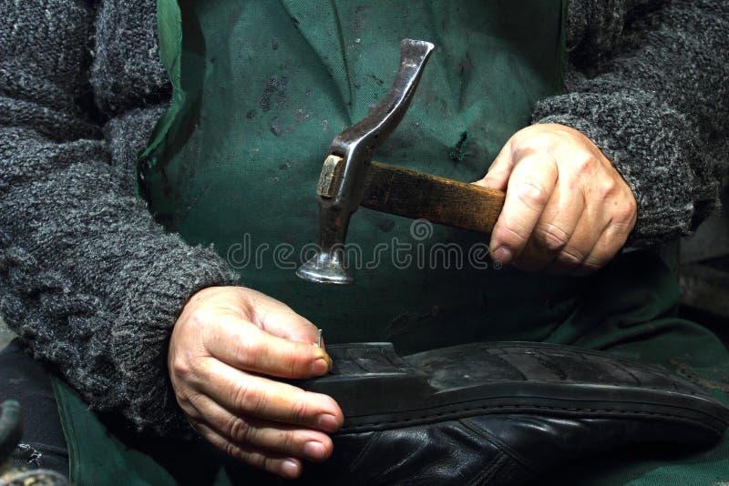 Trabalhadores a domicílio do sapateiro Trabalho duro no equipamento velho imagens de stock royalty free