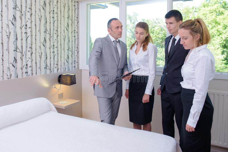 Trabalhadores e gerente das tarefas domésticas do serviço de hotel na sala de hotel fotografia de stock royalty free