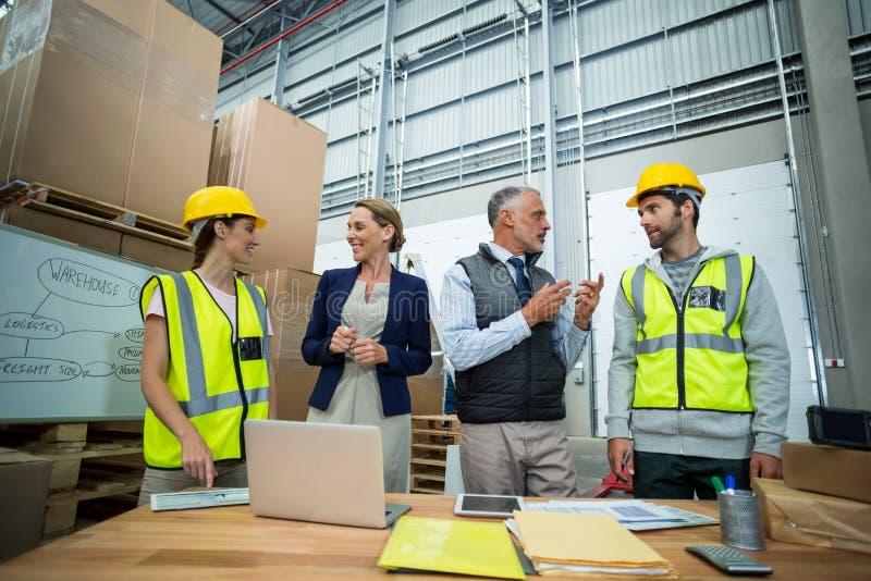 Trabalhadores e gerentes do armazém que interagem um com o otro imagens de stock royalty free