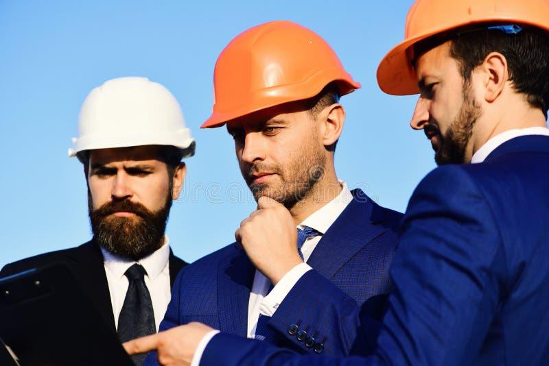 Trabalhadores e reunião da posse do coordenador sobre o projeto Os construtores discutem o plano fotografia de stock royalty free