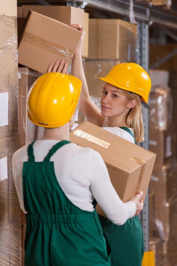 Trabalhadores fêmeas do armazenamento no armazém foto de stock