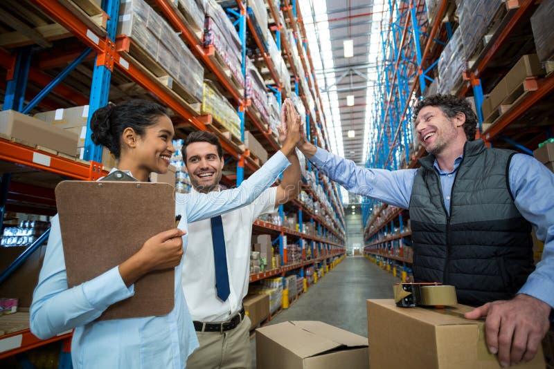 Trabalhadores felizes do armazém que dão a elevação cinco imagem de stock