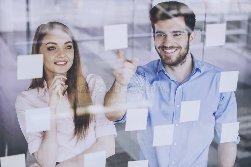 Trabalhadores felizes que olham em etiquetas com as ideias novas imagens de stock royalty free