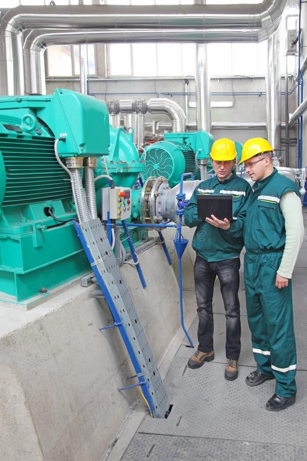 Trabalhadores industriais com caderno, trabalhos de equipa foto de stock
