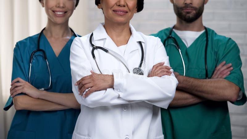 Trabalhadores médicos amigáveis que cruzam as mãos, prontas para ajudar, pessoal altamente qualificado imagens de stock royalty free