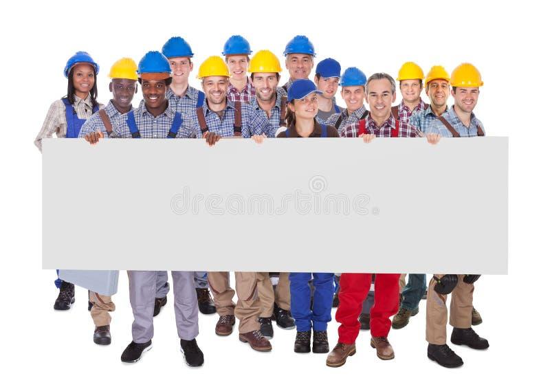 Trabalhadores manuais multi-étnicos que guardam a bandeira vazia fotos de stock