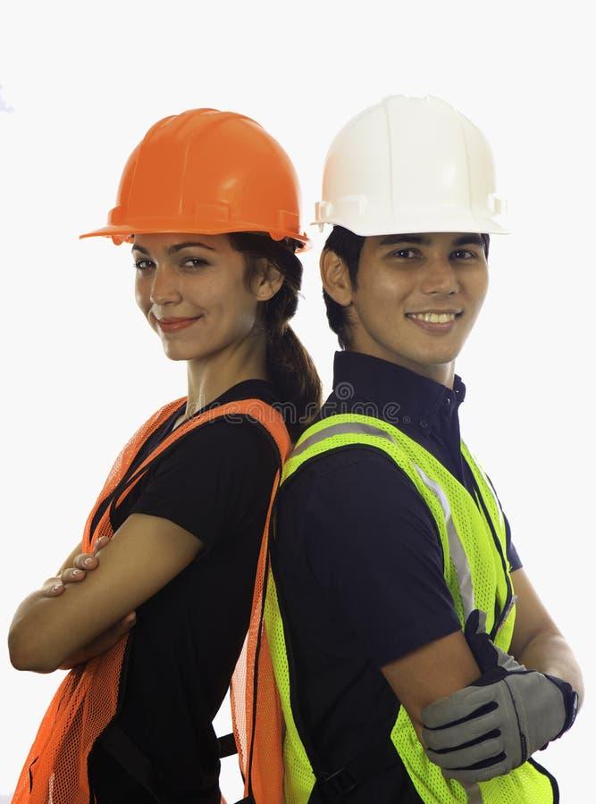 Trabalhadores masculinos e fêmeas do capacete de segurança foto de stock