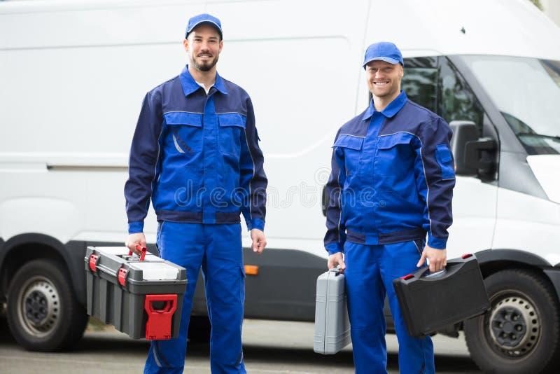 Trabalhadores masculinos felizes que guardam caixas de ferramentas fotografia de stock