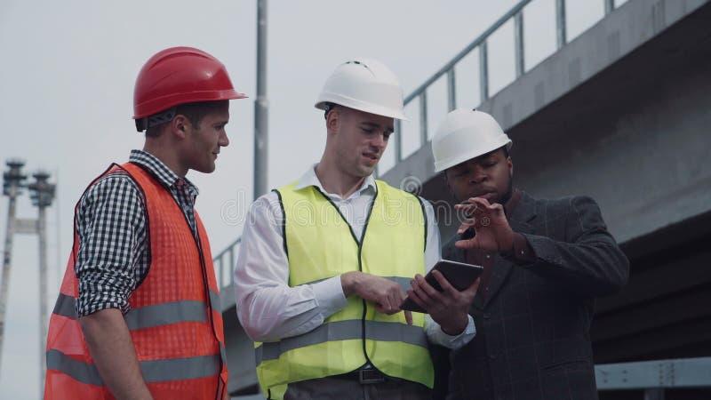 Trabalhadores nas vestes que mostram a chefe algo na tabuleta video estoque