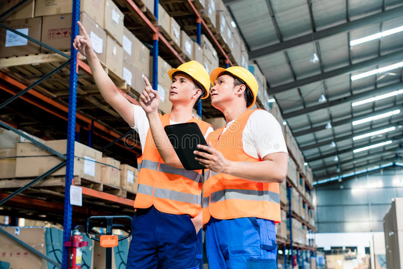 Trabalhadores no armazém da logística na lista de verificação da empilhadeira fotografia de stock