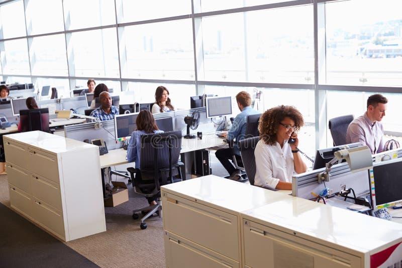 Trabalhadores ocasionalmente vestidos em um escritório de plano aberto ocupado imagem de stock